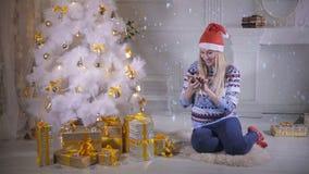 Une jeune femme vérifie son smartphone sous un arbre de Noël banque de vidéos