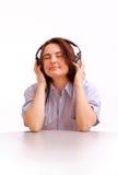 Une jeune fille écoute la musique sur des écouteurs Images stock