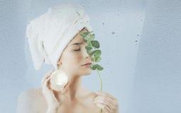 Une jeune fille après la prise d'un bain emploie une crème hydratante de corps et de visage sur un fond bleu Le concept des soins photographie stock