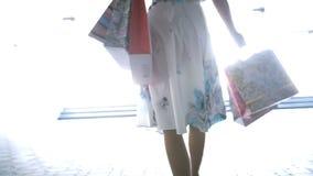 Une jeune fille avec des paquets va sur la transition clips vidéos