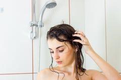 Une jeune fille avec du charme avec les cheveux humides a abaissé ses yeux et a nettoyé dans la douche Photos libres de droits