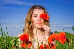 Une jeune fille avec du charme dans un domaine de pavot ferme un oeil avec une fleur de pavot un jour ensoleillé lumineux d'été Photo stock