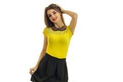 Une jeune fille avec du charme dans un T-shirt et une jupe jaunes sourit et tient sa main près des cheveux Images libres de droits