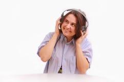 Une jeune fille avec le sourire d'écouteurs Photographie stock