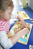 Une jeune fille avec un puzzle. Photo stock