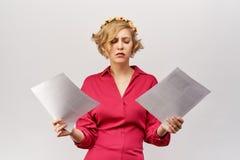 Une jeune fille blonde avec une vue perdue regarde les documents répandant ses mains devant elle dans la confusion et les mal com photo libre de droits