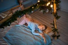 Une jeune fille blonde sourit mystérieusement et se trouve sur le lit dans un chandail bleu photo libre de droits