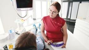 Une jeune fille ? une consultation avec une femme de dentiste en verres s'assied sur une chaise dans un bureau de stamotology E banque de vidéos