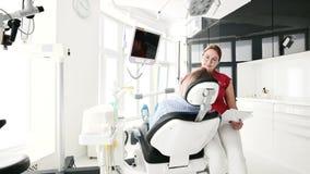 Une jeune fille ? une consultation avec une femme de dentiste en verres s'assied sur une chaise dans un bureau de stamotology E clips vidéos