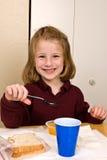 Jeune fille d'école mangeant le déjeuner Photos libres de droits