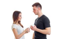 Une jeune fille dans l'amour et un type regardent l'un l'autre et tenant une tasse de thé chaud Photo stock
