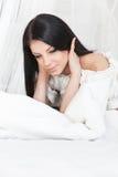 Une jeune fille dans le bonheur de matin sur son lit Photos libres de droits