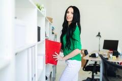 Une jeune fille dans le bureau retire des dossiers avec des documents Photos stock