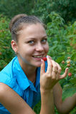 Une jeune fille dans le jardin avec des framboises dans la bouche Photo stock