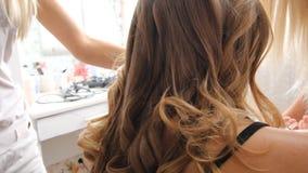 Une jeune fille dans le salon de beauté font la coiffure banque de vidéos