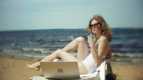 Une jeune fille dans un bikini blanc se trouve et la prend un bain de soleil sur un canapé sur la plage sablonneuse de mer et boi banque de vidéos