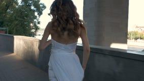 Une jeune fille dans un costume blanc court le long du remblai banque de vidéos