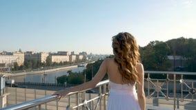 Une jeune fille dans un costume blanc marche sur la plate-forme d'observation clips vidéos