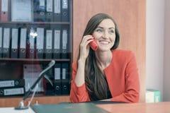 Une jeune fille dans un costume rouge s'assied de retour au travail, parlant au téléphone avec des amis Travail de bureau Image stock