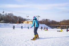 Une jeune fille dans un costume spécial pour l'amusement et les sports d'hiver apprend à monter un surf des neiges un jour ensole photographie stock