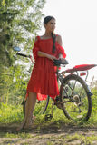 Une jeune fille dans une robe rouge se tient près d'une bicyclette avec un parapluie rouge À l'arrière-plan il y a une forêt Images stock