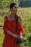 Une jeune fille dans une robe rouge se tient près d'une bicyclette avec un parapluie rouge À l'arrière-plan il y a une forêt Photo stock