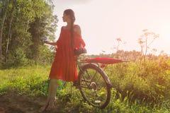 Une jeune fille dans une robe rouge se tient près d'une bicyclette avec un parapluie rouge À l'arrière-plan il y a une forêt Photo libre de droits