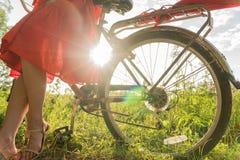 Une jeune fille dans une robe rouge se tient près d'une bicyclette avec un parapluie rouge À l'arrière-plan les rayons du soleil Photos libres de droits