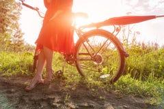 Une jeune fille dans une robe rouge se tient près d'une bicyclette avec un parapluie rouge À l'arrière-plan les rayons du soleil Photographie stock libre de droits