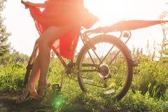 Une jeune fille dans une robe rouge se tient près d'une bicyclette avec un parapluie rouge À l'arrière-plan les rayons du soleil Images stock