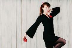 Une jeune fille de danse dans la robe noire, avec des castagnettes, backg léger photographie stock