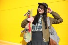 Une jeune fille de hippie monte une planche à roulettes Amies f de filles Images libres de droits