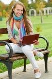 Une jeune fille de sourire avec l'ordinateur portatif à l'extérieur Photo stock
