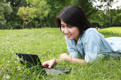 Une jeune fille de sourire avec l'ordinateur portatif à l'extérieur Photo libre de droits