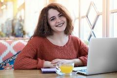 Une jeune fille de sourire rousse d'étudiant s'asseyant dans un café ensoleillé photographie stock