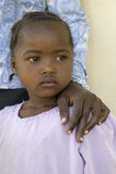 Une jeune fille du Kenya, atteinte du HIV/SIDA, se tient près de Khadija Rama, la fondatrice de Pepo La Tumaini Jangwani, Communa images stock