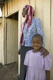 Une jeune fille du Kenya, atteinte du HIV/SIDA, se tient près de Khadija Rama, la fondatrice de Pepo La Tumaini Jangwani, Communa image stock