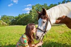Une jeune fille embrasse le cheval Photographie stock libre de droits