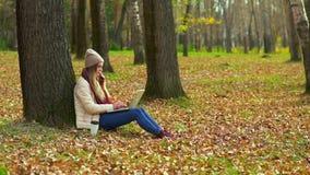 Une jeune fille en parc d'automne près d'un arbre, introduisant au clavier un ordinateur portable, fonctionnant banque de vidéos