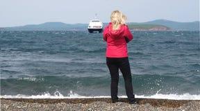 Une jeune fille en rouge attend l'arrivée du ferry à l'île Photos libres de droits