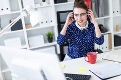 Une jeune fille en verres s'assied dans le bureau à la table, met dessus des écouteurs et des regards au moniteur image stock