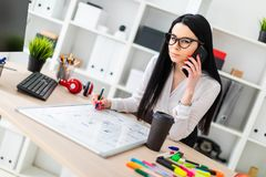 Une jeune fille en verres se tient près d'une table, parle au téléphone et dessine un marqueur sur un conseil magnétique image stock