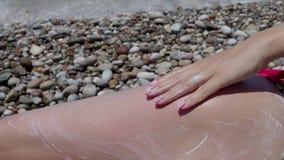 Une jeune fille enduit une protection solaire sur ses pieds de sa main sur la plage 4 K clips vidéos
