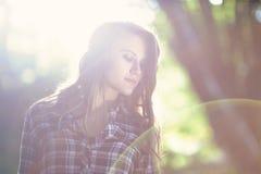 Une jeune fille entourée par lumière du soleil Image libre de droits