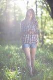 Une jeune fille entourée par lumière du soleil Photo libre de droits