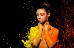 Une jeune fille est baignée en peinture jaune et orange images stock