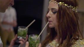 Une jeune fille et des cocktails potables d'un homme à une partie banque de vidéos