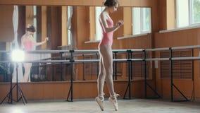 Une jeune fille exécute avec élégance des tours d'acrobaties dans le studio image libre de droits