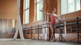 Une jeune fille exécute avec élégance des tours d'acrobaties dans le studio images stock
