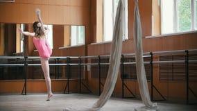 Une jeune fille exécute avec élégance des tours d'acrobaties dans le studio, au ralenti banque de vidéos